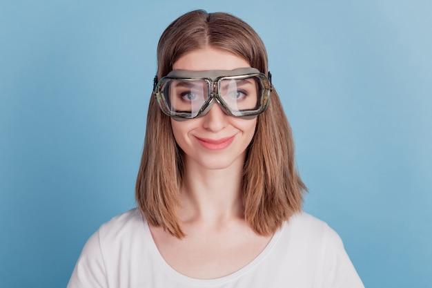 Portret van charmante vrolijke snowboarder rijder dame draagt een bril op blauwe achtergrond