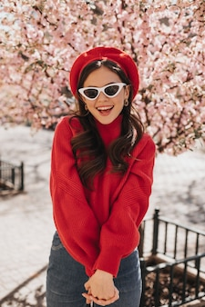 Portret van charmante vrouw in rode baret en glazen op achtergrond van sakura. dame in jeans en lichte sweater die van wandeling in bloeiende tuin geniet