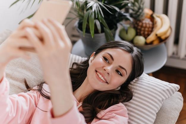 Portret van charmante vrouw liggend op een kussen in de woonkamer en selfie te nemen