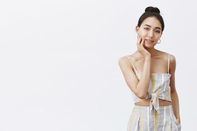 Portret van charmante vrouw met haar in knot, gezicht zachtjes aanraken en starend, ontspannen en sensueel, vrouwelijk over grijze muur