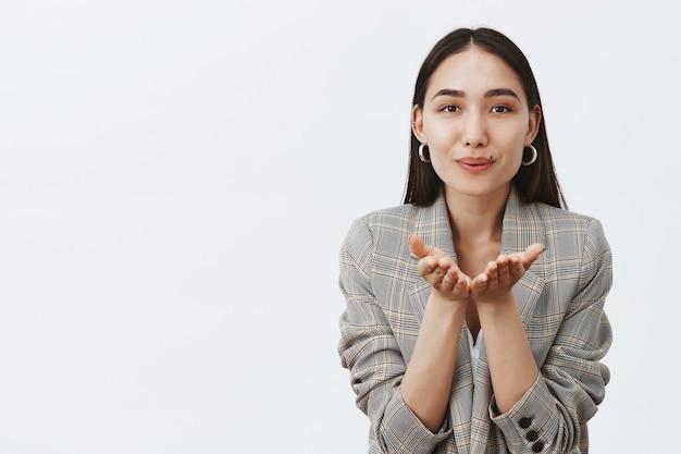 Portret van charmante vrouwelijke volwassen vrouw in trendy jas, glimlachend, handpalmen vasthouden in de buurt van mond en mwah blazen, sympathie en zorg betuigen