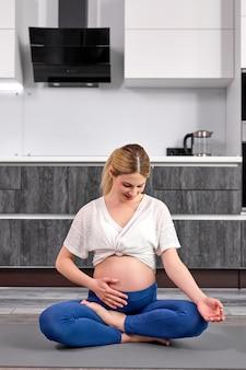 Portret van charmante zwangere vrouw streelde grote naakte buik zitten rust op de vloer met gekruiste benen