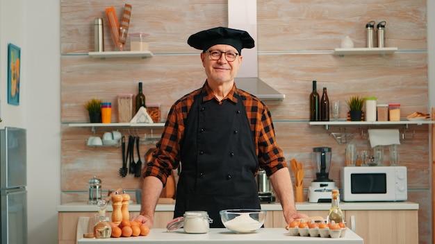 Portret van chef-kok die bonete draagt die camera bekijkt en glimlacht. gepensioneerde oudere bakker in keukenuniform die gebakingrediënten voorbereidt op houten tafel, klaar om zelfgemaakt lekker brood, gebak en pasta te koken