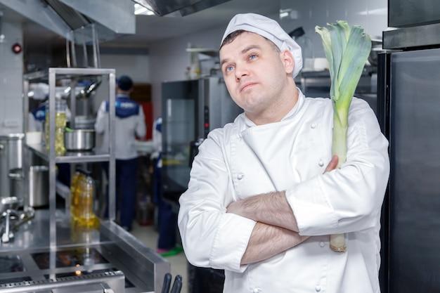 Portret van chef-kok in restaurantkeuken die en een prei denken houden