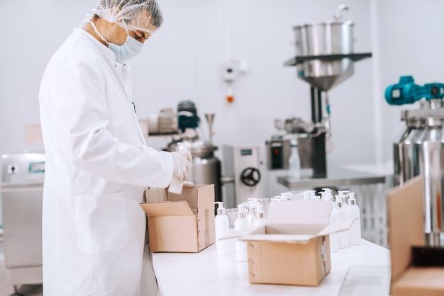 Portret van chemische werknemer in steriele uniforme verpakking vloeibare zepen in dozen
