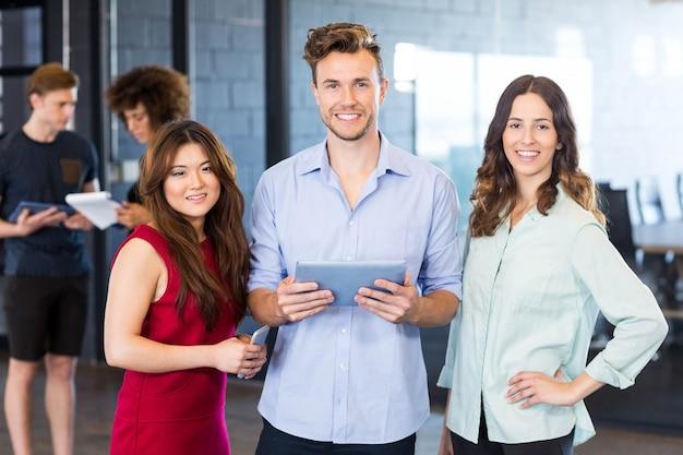 Portret van collega's die een digitale tablet en het glimlachen houden