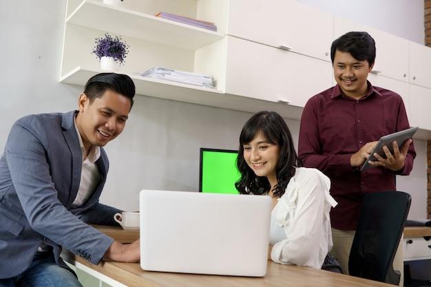 Portret van collega's die met plezier en plezier werken en elkaar helpen op kantoor