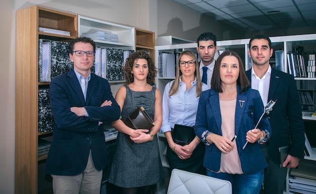 Portret van collega's op kantoor die tegen boekenkasten staan