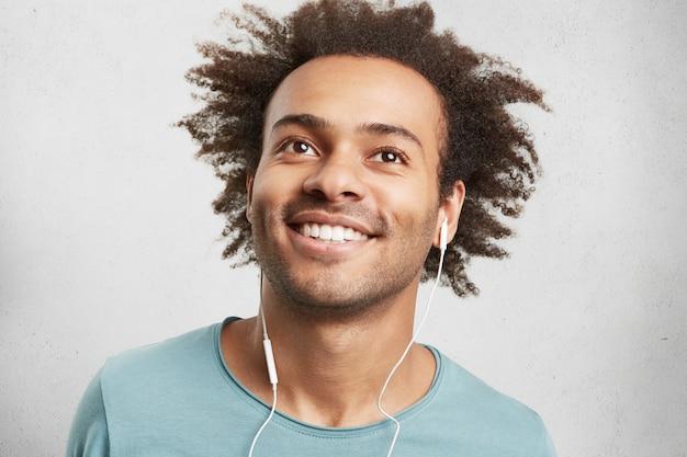 Portret van coole jonge zwarte man met krullend haar, heeft vrolijke uitdrukking