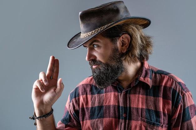 Portret van cowboy in hoed. portret van een man met een cowboyhoed, een pistool. portret van een cowboy. west, geweren. portret van een cowboy. amerikaanse bandiet in masker, westerse man met hoed.