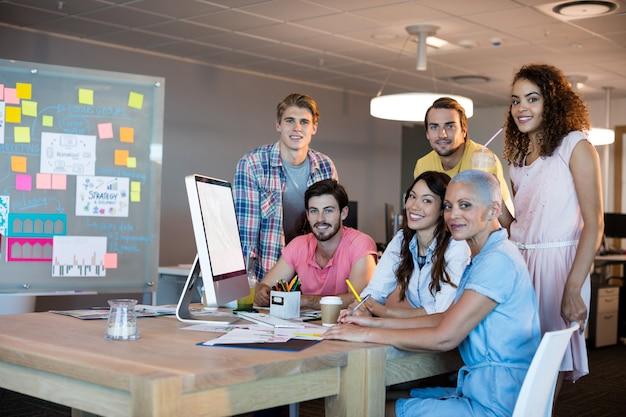 Portret van creatieve business team samen te werken op desktop pc op kantoor