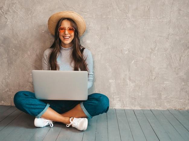 Portret van creatieve jonge glimlachende vrouw in zonnebril. mooi meisje, zittend op de vloer in de buurt van grijze muur ... typen en zoeken naar informatie