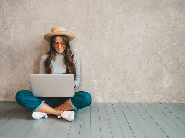 Portret van creatieve jonge glimlachende vrouw in zonnebril. mooie meisjeszitting op de vloer dichtbij grijze muur.