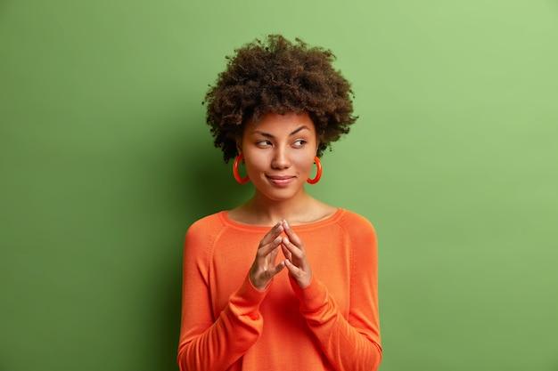Portret van creatieve jonge vrouw met donkere huid steekt vingers en ziet er mysterieus uit opzij