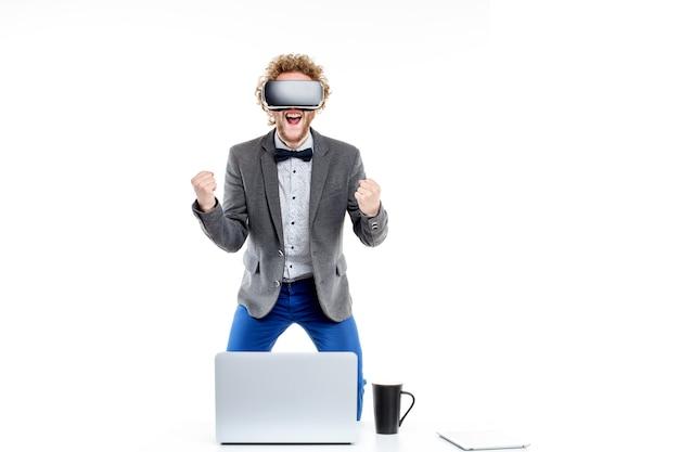 Portret van curly-haired elegante zakenman in vr-bril met hand in vuist op stoel aan tafel met gadgets