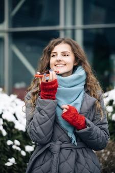Portret van curly haired vrouw met telefoon die het ai audiobericht van de stemherkenning op de telefoon gebruikt