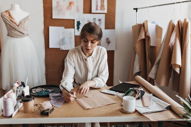 Portret van dame die schets trekt en jurk ontwerpt