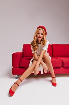Portret van dame in rode schoenen en baret die zich voordeed op de bank. sierlijke witte vrouw in jurk koelen tijdens fotoshoot.