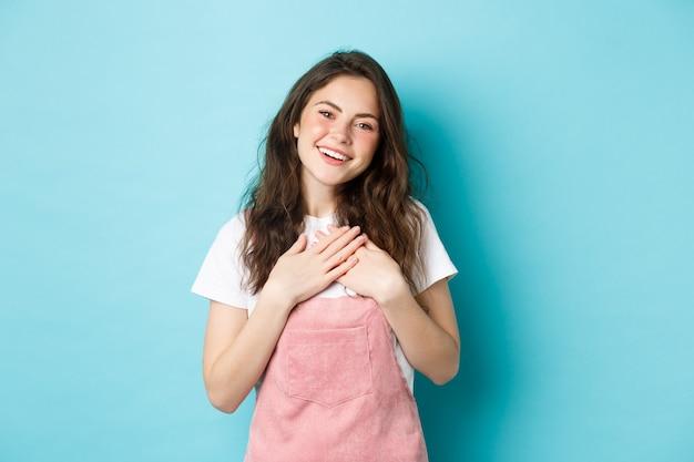 Portret van dankbare glimlachende jonge vrouw met krullend kapsel, zomermake-up, hand in hand op het hart en oprecht kijkend, dankbaarheid uiten, je bedanken, blauwe achtergrond.