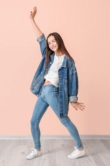 Portret van dansende jonge vrouw in de buurt van kleur oppervlak