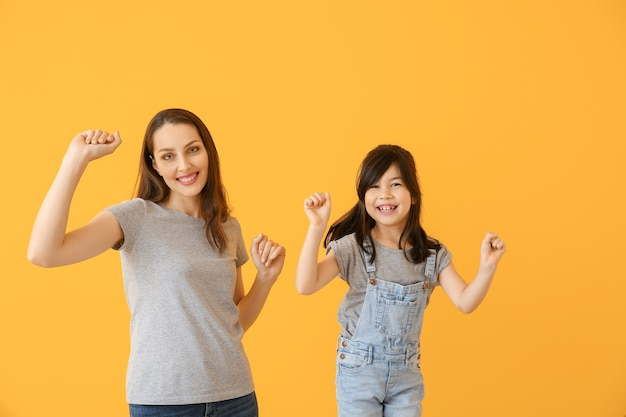 Portret van dansende moeder met dochter op kleuroppervlak