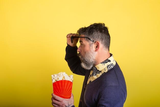 Portret van de aantrekkelijke mens met baard en zonnebril die een doos popcorn in profiel in verbaasde camera houden die omhoog de glazen op gele achtergrond bekijken.