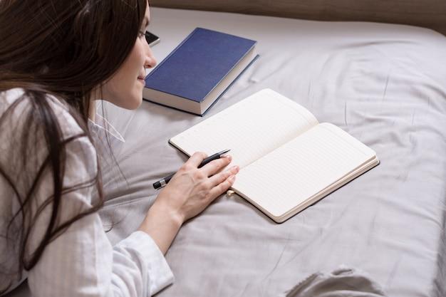 Portret van de achterkant van een brunette vrouw liggend in bed met een boek en een dagboek, records. planning, verlangens, doelen, geschriften, creativiteit.