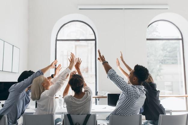Portret van de achterkant van vermoeide studenten die zich uitstrekken na lang werk. indoor foto van kantoorpersoneel gek rond tijdens bijeenkomst in conferentiezaal met grote ramen.
