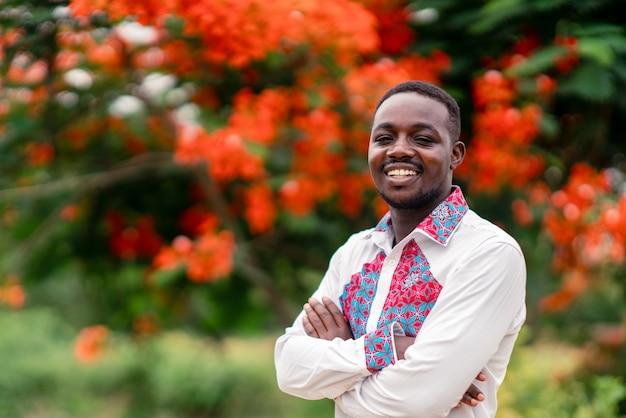 Portret van de afrikaanse mens die inheemse traditionele kleurrijke doek met glimlach dragen en gelukkig.