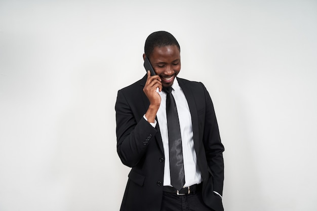 Portret van de afrikaanse mens die terwijl het spreken op de telefoon met grijze muur glimlacht