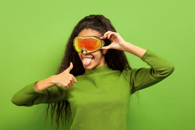 Portret van de afro-amerikaanse jonge brunette vrouw in skimasker op groen