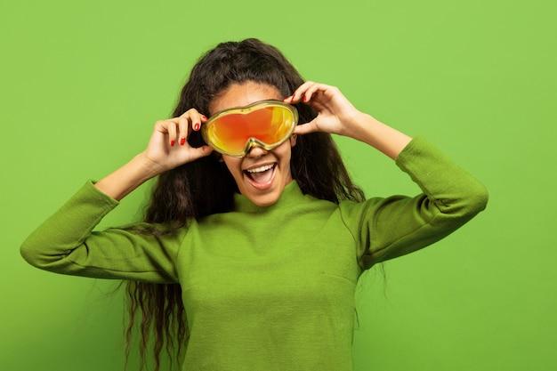 Portret van de afro-amerikaanse jonge brunette vrouw in skimasker op groene studio achtergrond. concept van menselijke emoties, gezichtsuitdrukking, verkoop, advertentie, wintersport en vakanties. glimlachen, bril dragen.