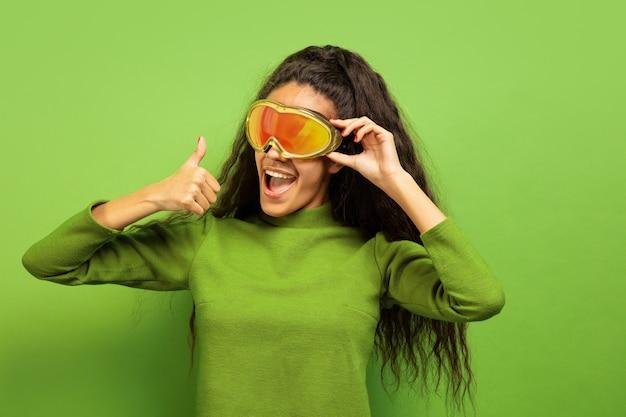 Portret van de afro-amerikaanse jonge brunette vrouw in skimasker op groene studio achtergrond. concept van menselijke emoties, gezichtsuitdrukking, verkoop, advertentie, wintersport en vakanties. glimlachend, duim omhoog.