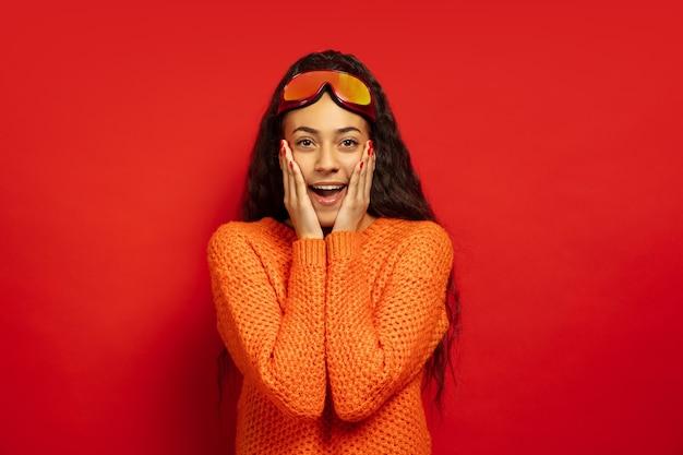 Portret van de afro-amerikaanse jonge brunette vrouw in skimasker op rode studio achtergrond. concept van menselijke emoties, gezichtsuitdrukking, verkoop, advertentie, wintersport en vakanties. verbaasd, verbaasd.