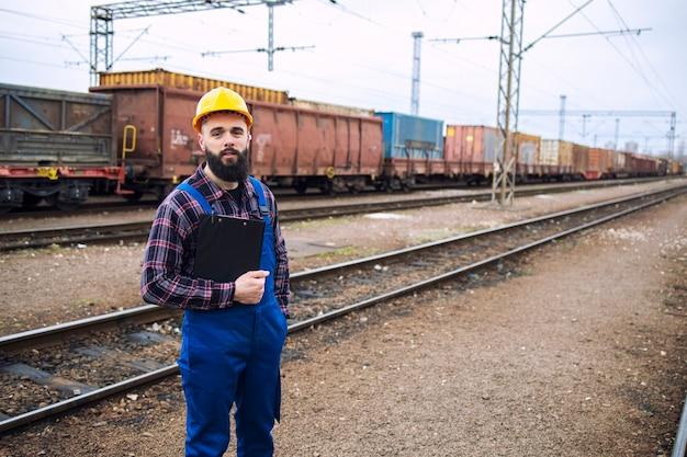 Portret van de arbeidersarbeider van de railroader met klembord die zich door de spoorlijnen en de goederentrein van de lading op de achtergrond bevinden
