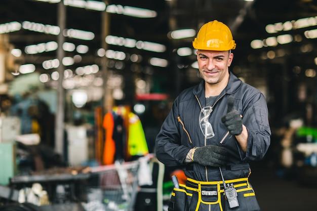 Portret van de arbeidersingenieur die van de voormanarbeid in industriële fabriek werken en voor veiligheidskostuum oppassen