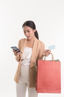 Portret van de aziatische creditcard van de vrouwenholding en slimme telefoon voor het winkelen online betaling en kleurrijke het winkelen zakken