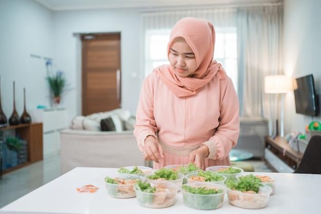 Portret van de aziatische moslimverkoper die van het vrouwenvoedsel haar product thuis keuken voorbereiden