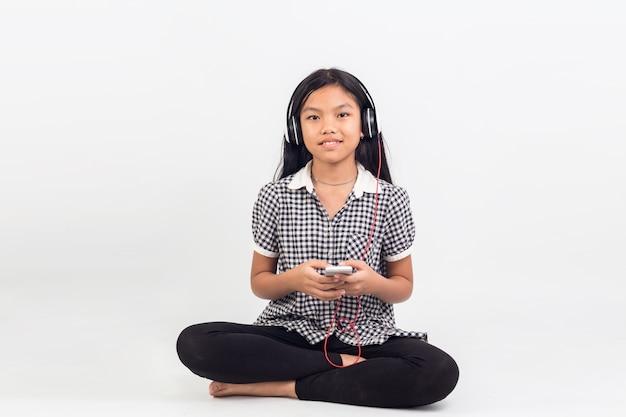 Portret van de aziatische zitting van het kinderenmeisje die aan geïsoleerde muziek luisteren