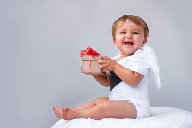 Portret van de baby met engelenvleugels met de gift in handen op grijs