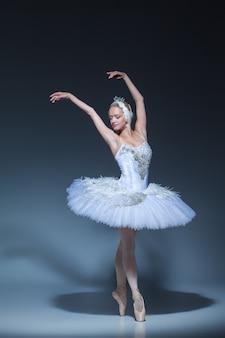 Portret van de ballerina in de rol van een witte zwaan op blauwe achtergrond Gratis Foto