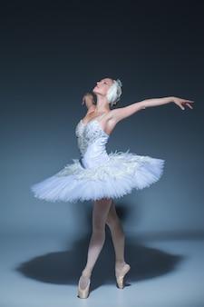 Portret van de ballerina in de rol van een witte zwaan op blauwe achtergrond