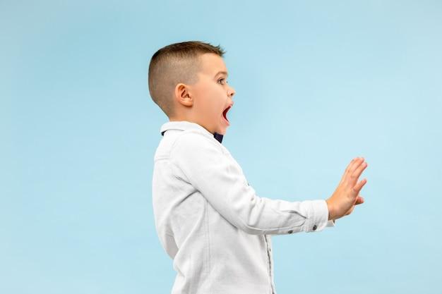 Portret van de bange jongen. tiener status geïsoleerd op trendy blauwe studio achtergrond. mannelijk halflang portret.
