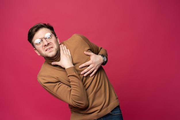 Portret van de bange man geïsoleerd op trendy roze achtergrond.