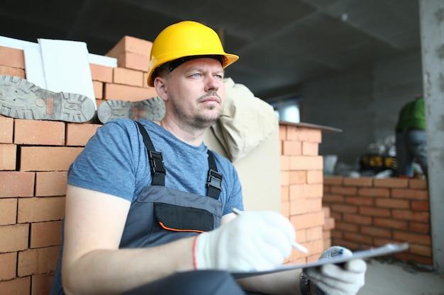 Portret van de betrokken mens die weg met pensiveness kijken. constructeur houdt planmap vast en schrijft er iets in. bebaarde specialist die over werkplan denkt. bouwconcept