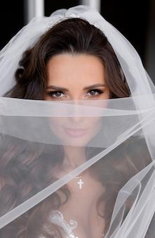 Portret van de blik van een aantrekkelijke donkerbruine bruid door de sluier
