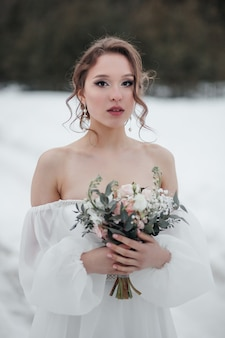 Portret van de bruid die een boeket vasthoudt. fotograferen in de winter