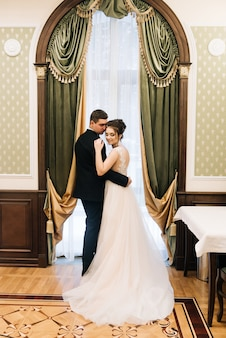 Portret van de bruid en bruidegom in een luxe interieur in de buurt van het raam.