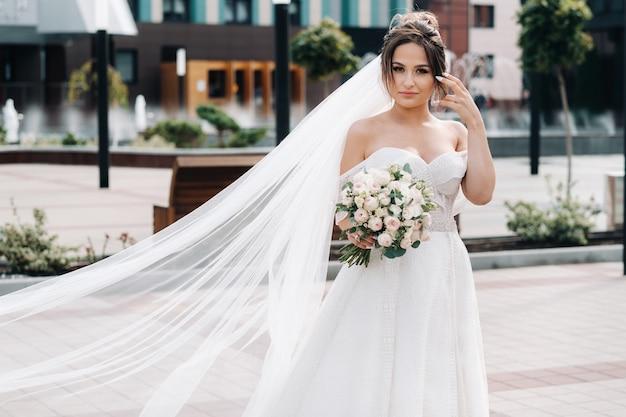 Portret van de bruid in de stad bij de fontein. een prachtige jonge bruid met krullend haar.