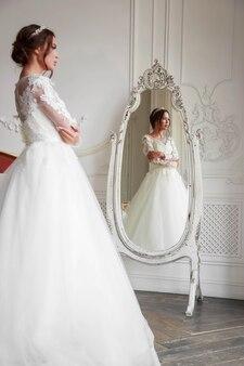 Portret van de bruid in de weerspiegeling van de spiegel in een lichte studio, met make-up en styling